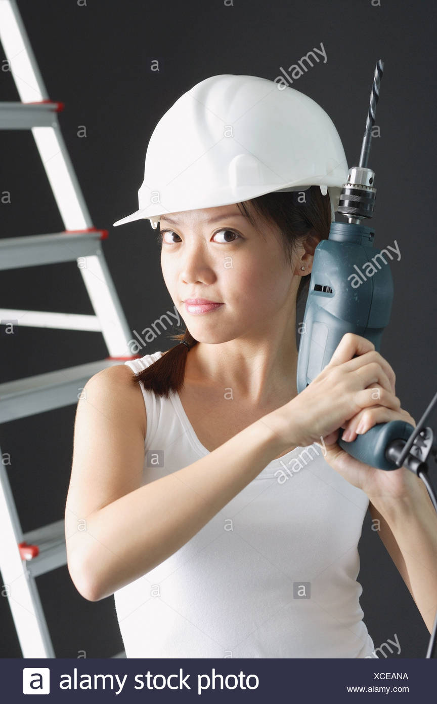 Young woman in hard hat, holding drill - Stock Image