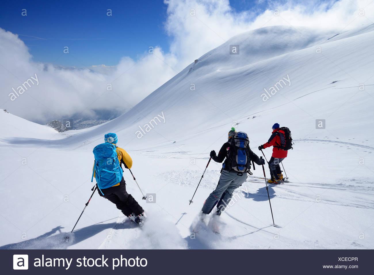 Three backcountry skiers downhill skiing from Monte Pesco Falcone, Rava del Ferro, Maiella, Abruzzo, Italy - Stock Image