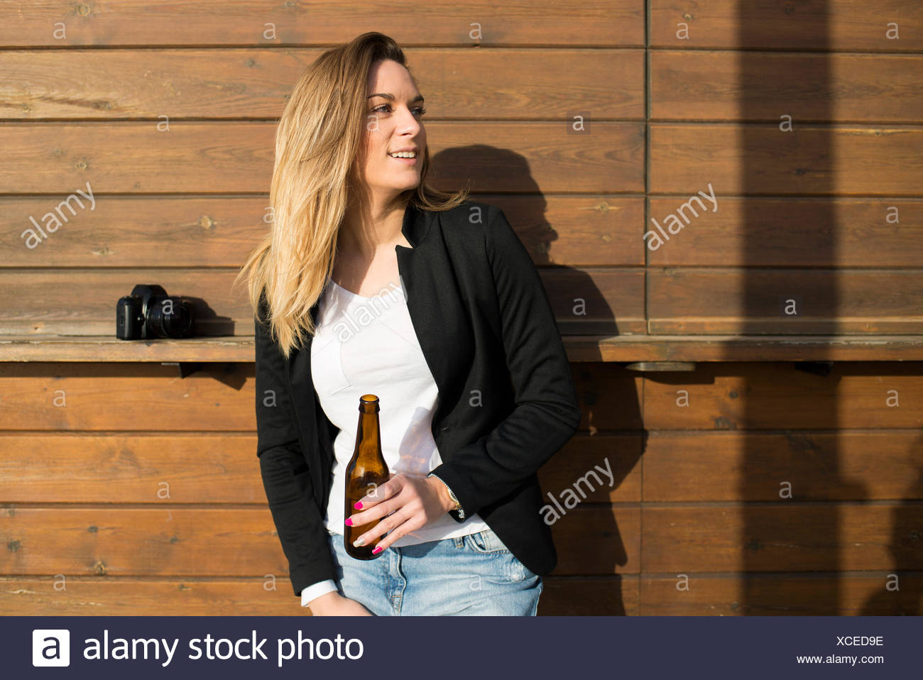 Smiling woman with bottle of beer watching something - Stock Image
