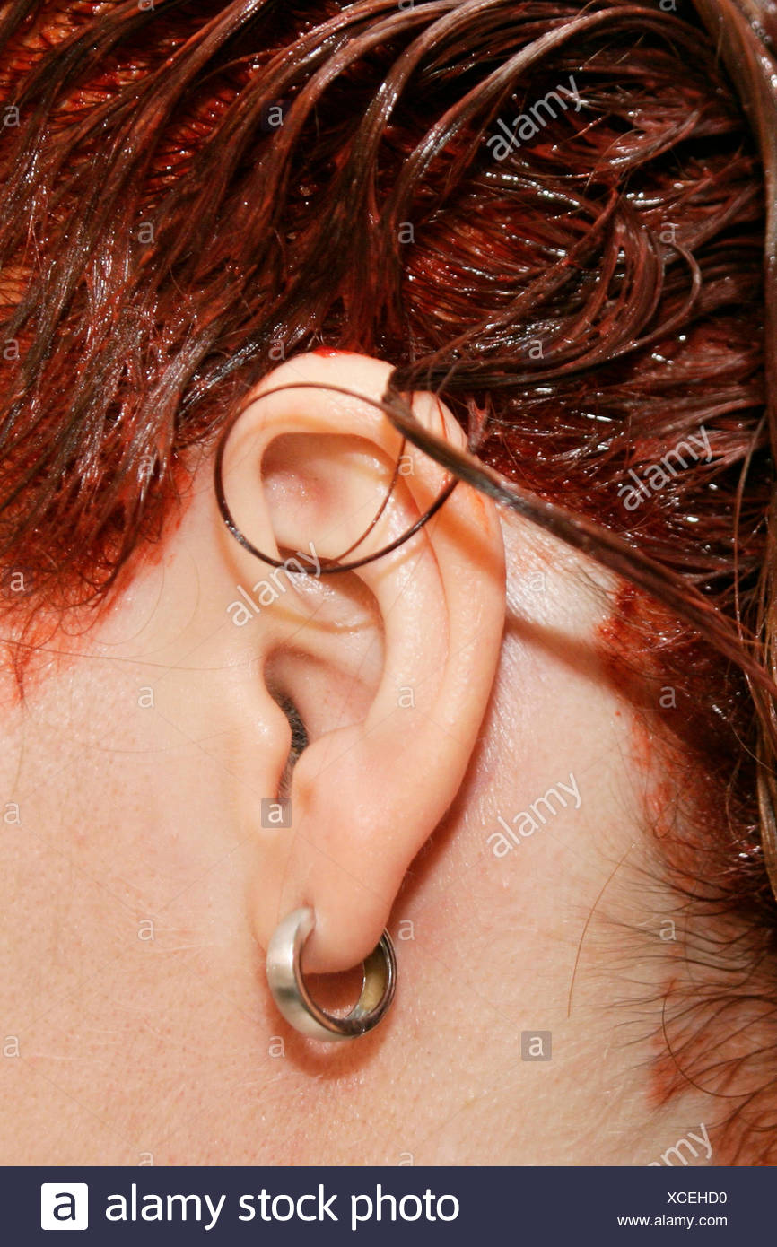 ear and dyed red hairs of a woman - Stock Image