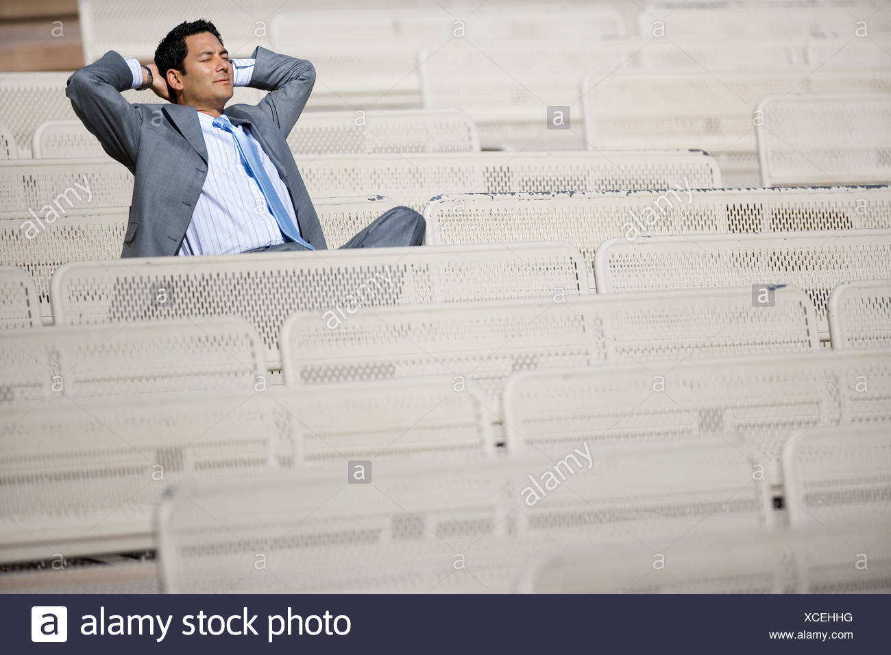 Businessman in grey suit sitting in empty stadium seat hands behind head eyes closed smiling - Stock Image