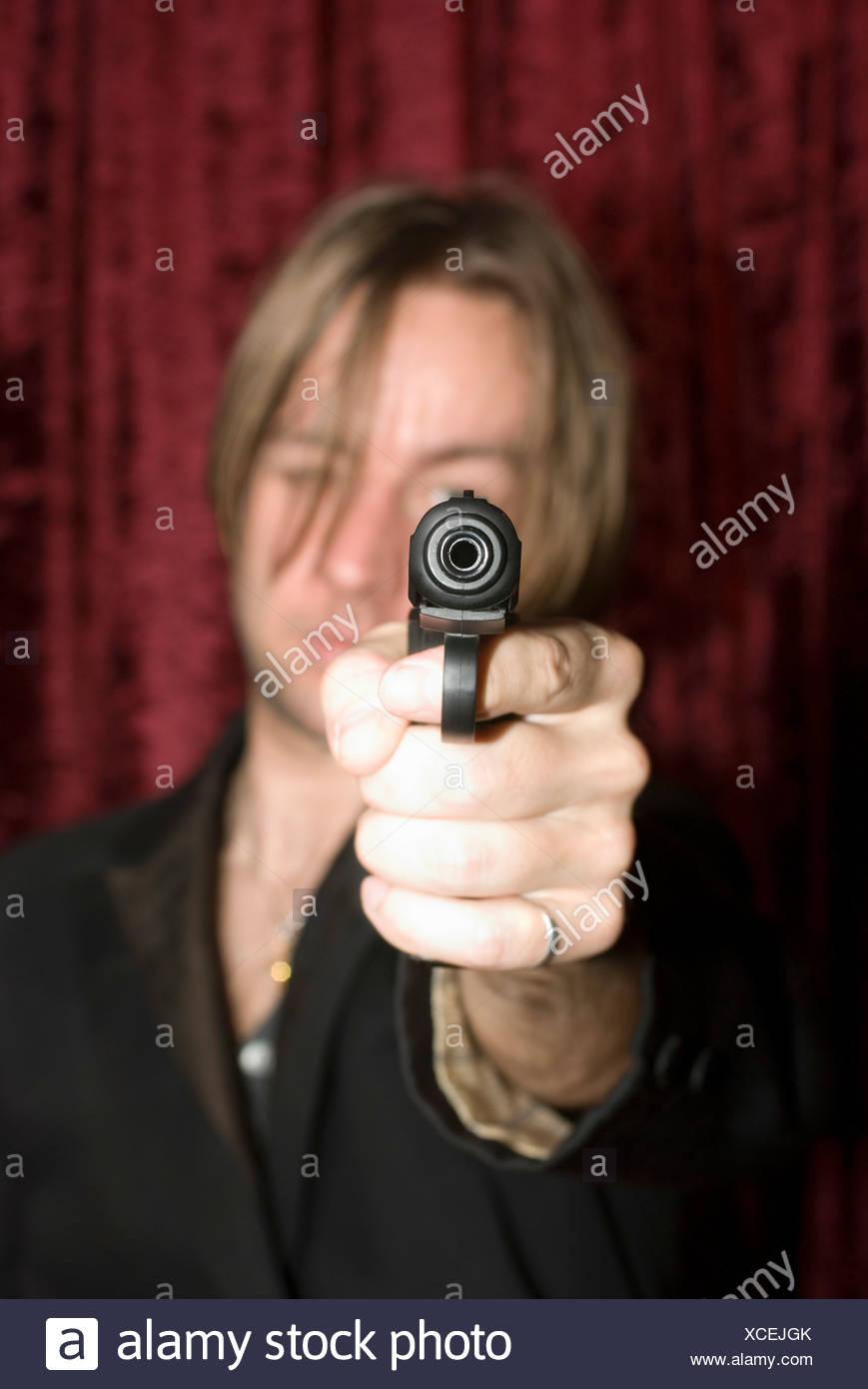 A man aiming a gun - Stock Image
