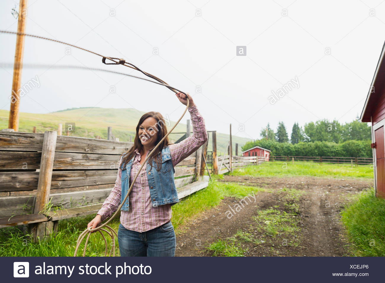Smiling woman spinning lasso on farm - Stock Image