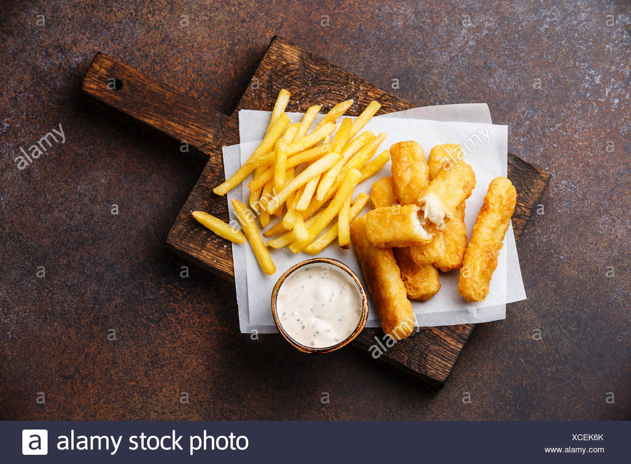 Fish fingers and Chips british fast food with tartar sauce on dark background - Stock Image