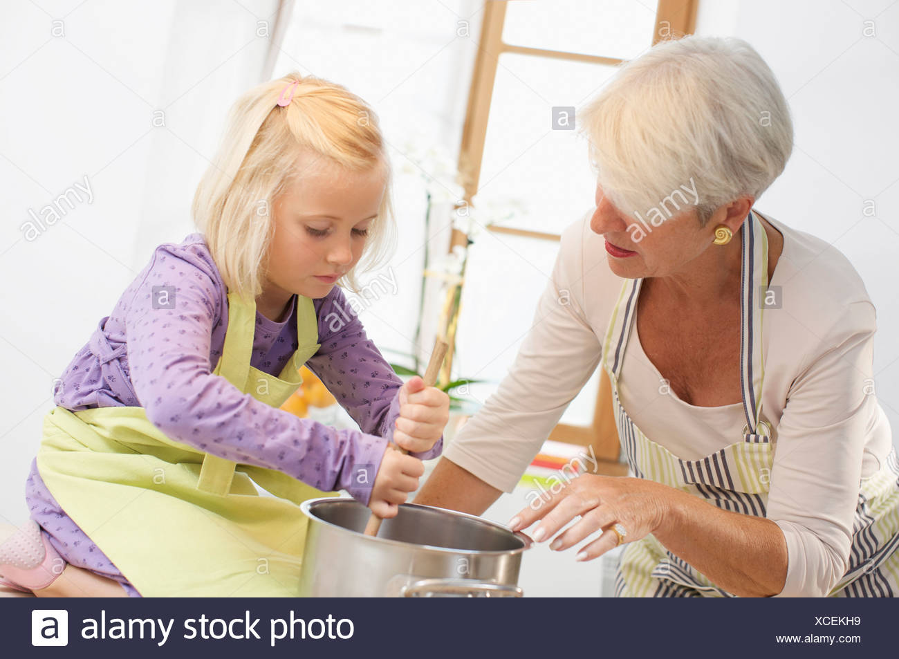 girl with grandmother cooking jam - Stock Image