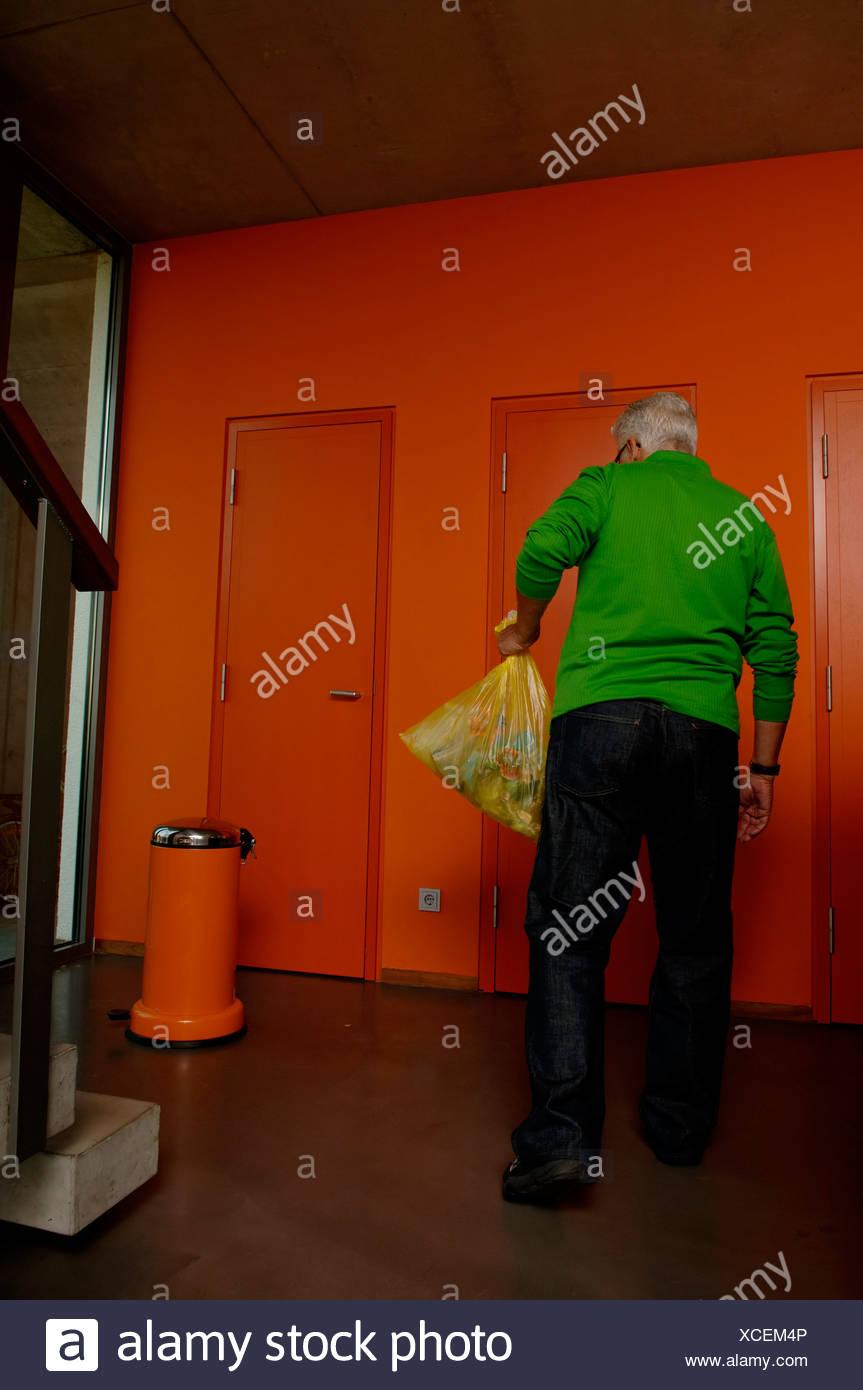 Senior man carrying a rubbish bag - Stock Image
