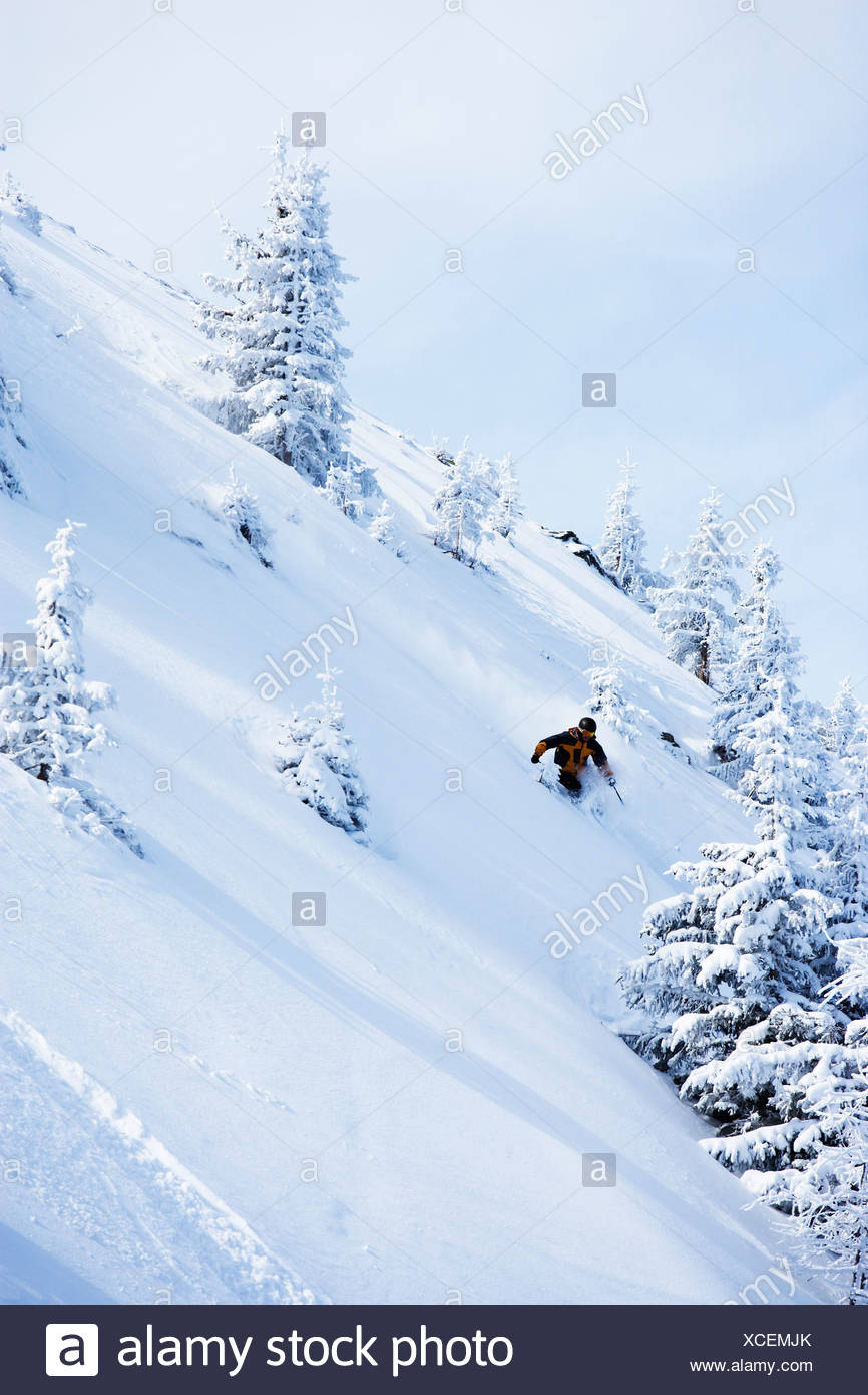Man in black & orange outfit off-piste. - Stock Image