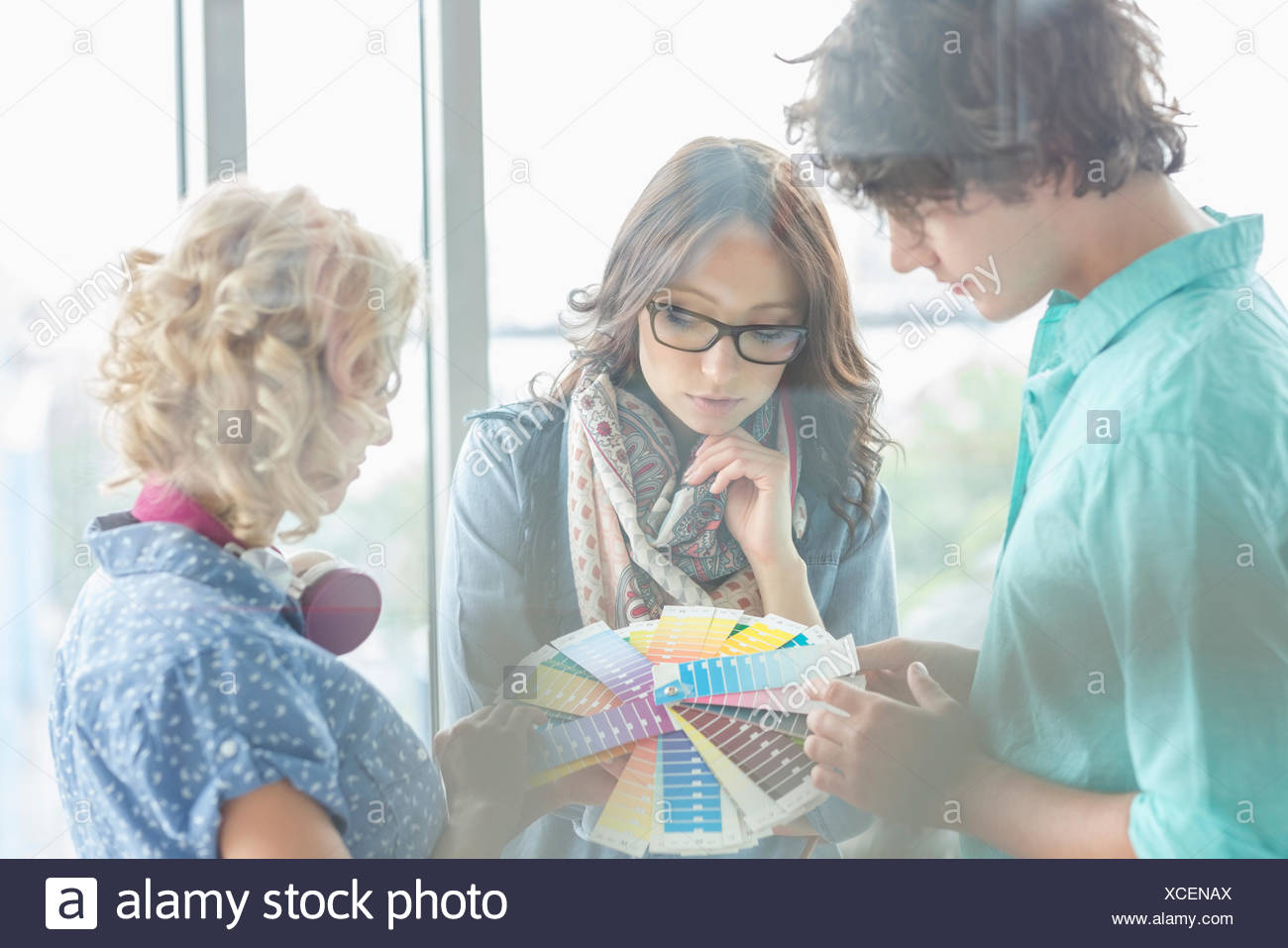 Creative businesspeople analyzing color swatches in office - Stock Image