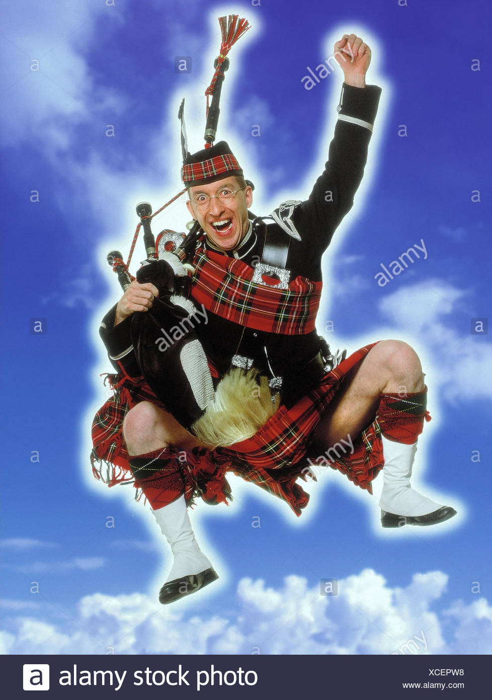 Bulkheads, kilt, bagpipes, caper, gesture, enthusiasm, cloudy sky studio, man, national costume, clothes, traditionally, glasses, cheering, joy, success, crack, jump - Stock Image