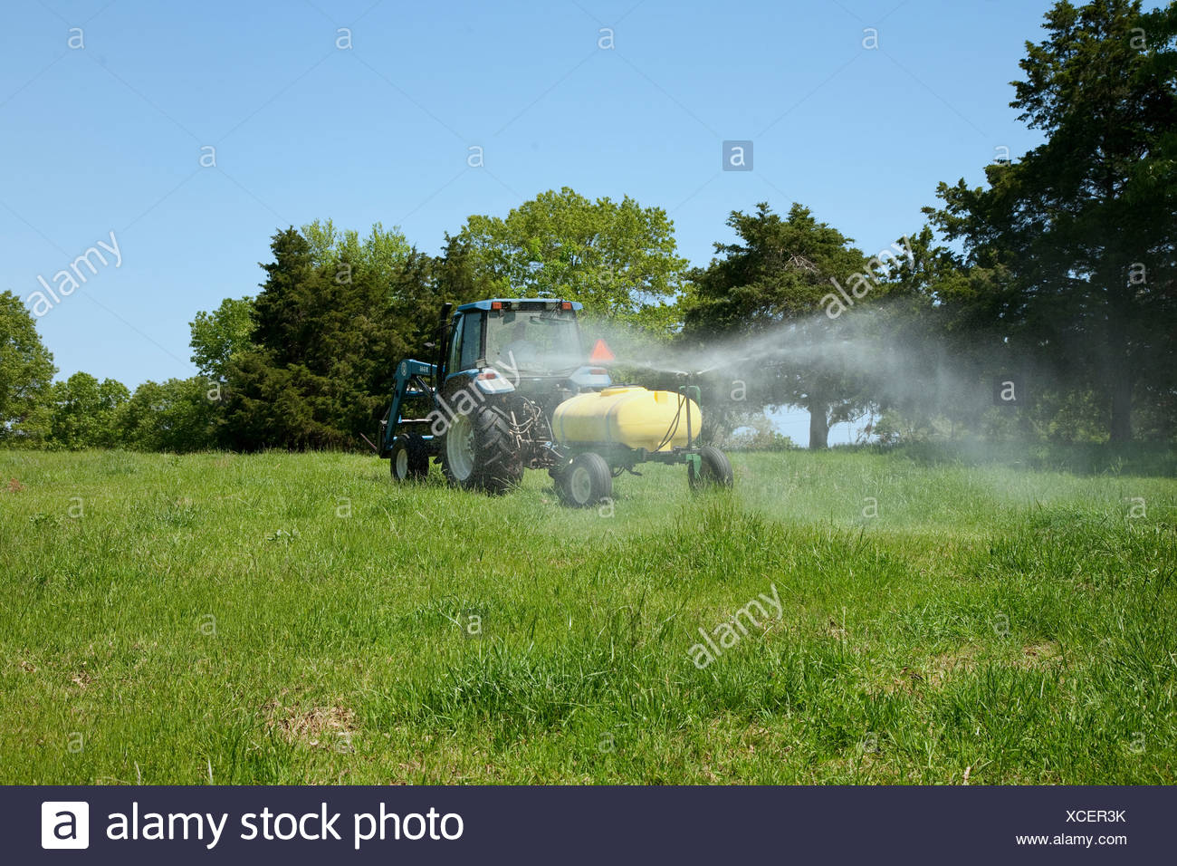 Spraying herbicide on a pasture used for grazing beef cattle. The herbicide is to control broadleaf weeds / Arkansas, USA. - Stock Image