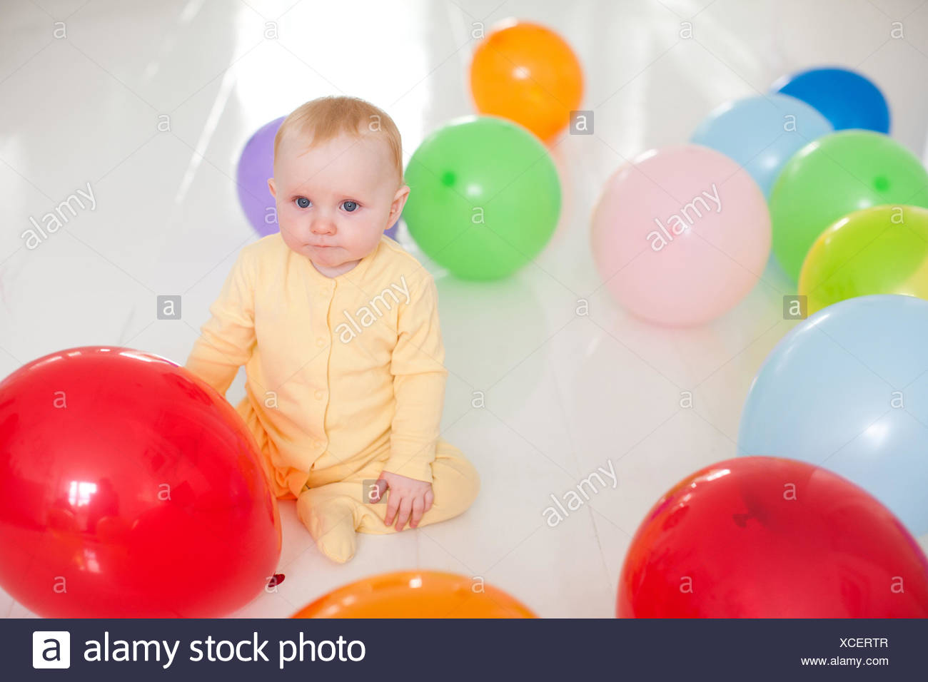 Curious baby with balloons - Stock Image