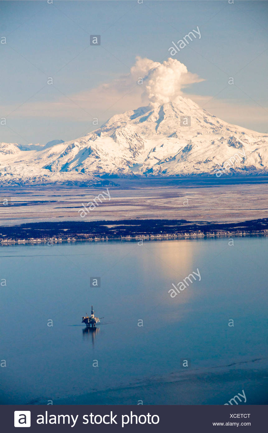 Alaska, Cook Inlet. Redbout volcano aerial with offshore oil platforms in Cook Inlet. Steam plume is visible from the mountain. - Stock Image