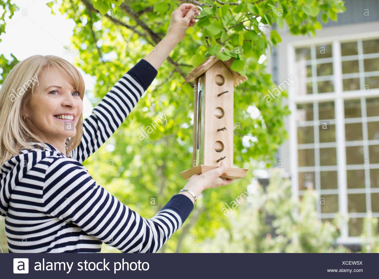 mature woman hanging a bird feeder - Stock Image