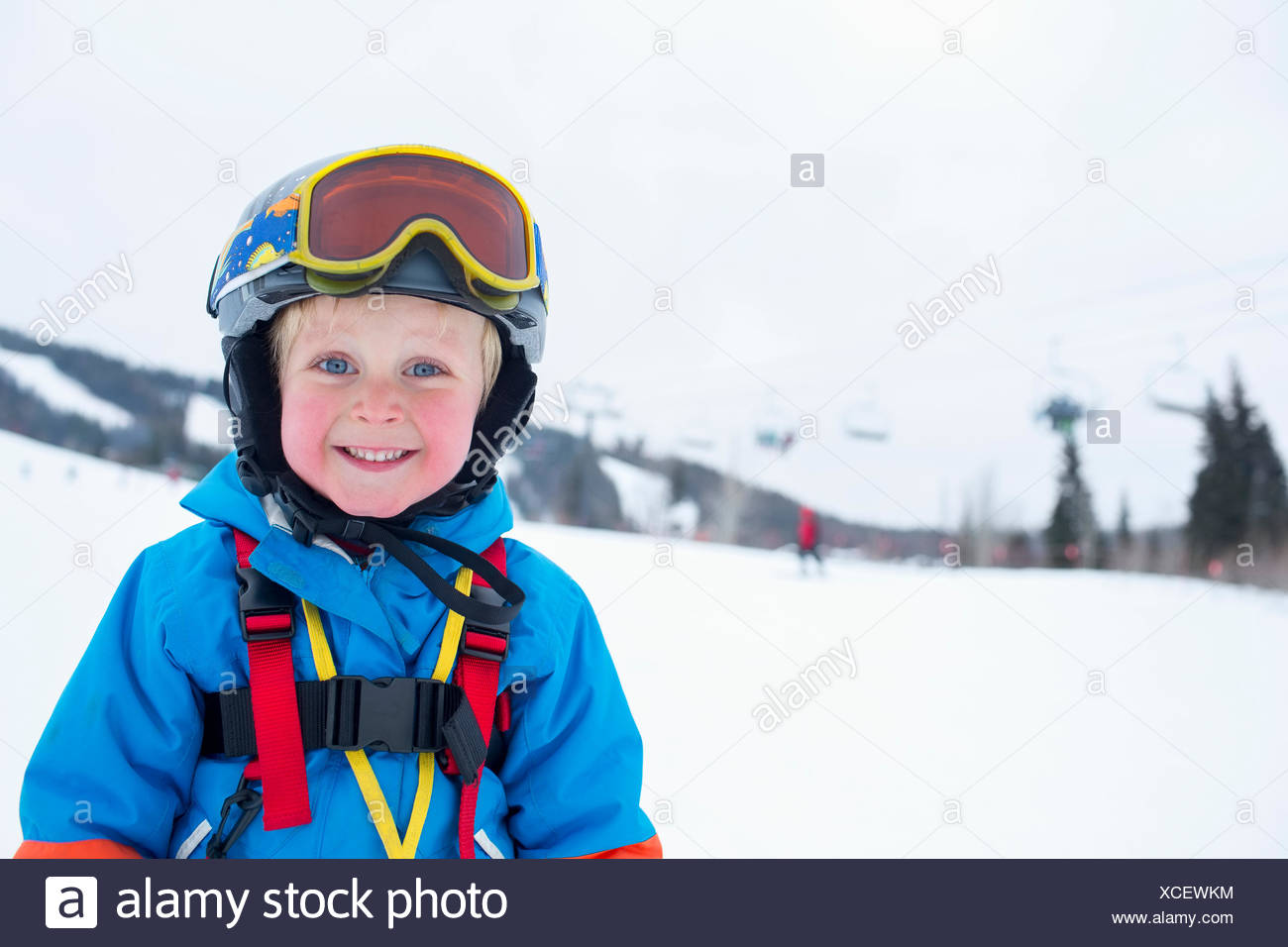 Smiley little boy (5) wearing ski suit in mountains - Stock Image