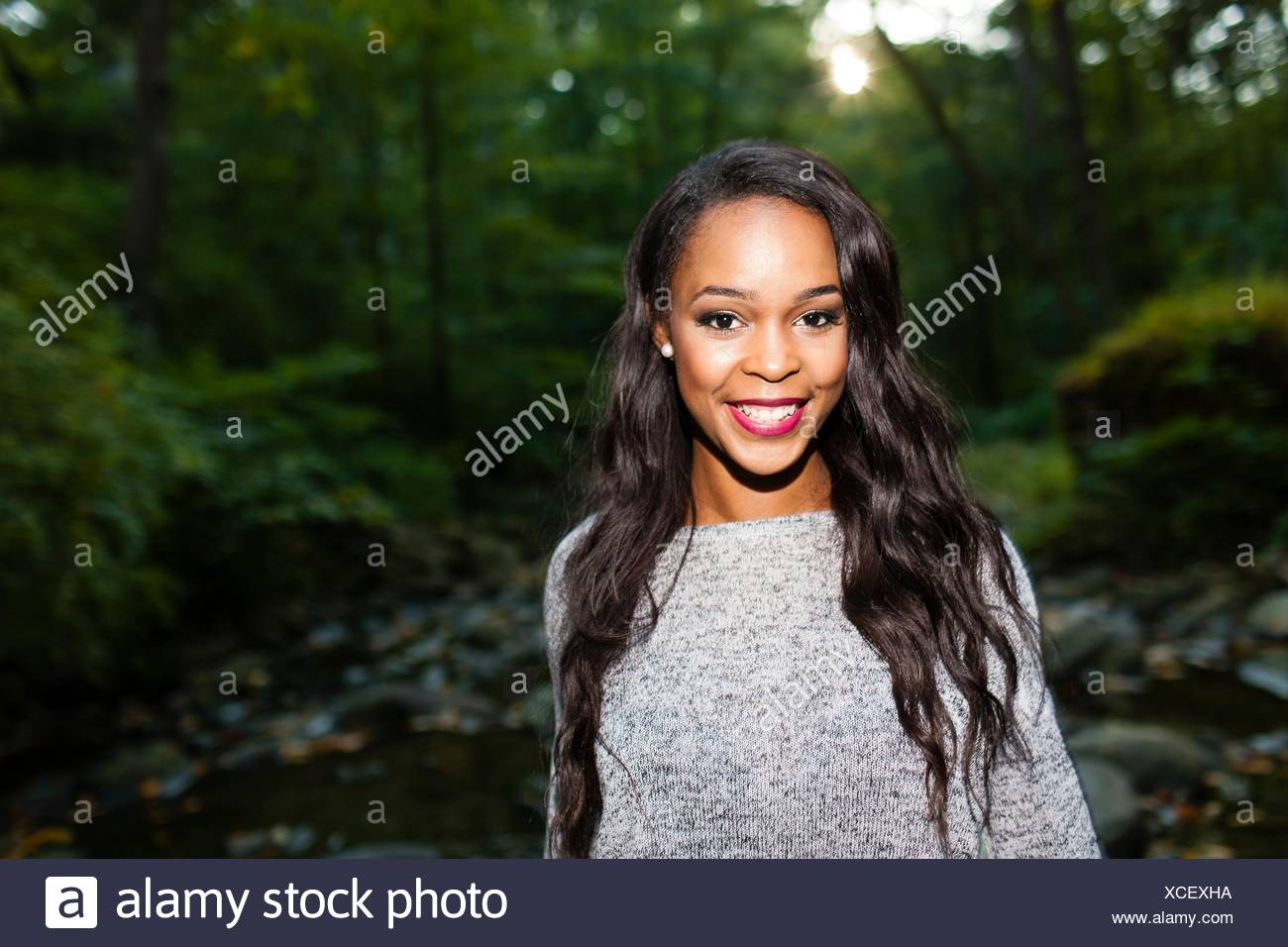 Portrait of happy young woman in darkened forest - Stock Image