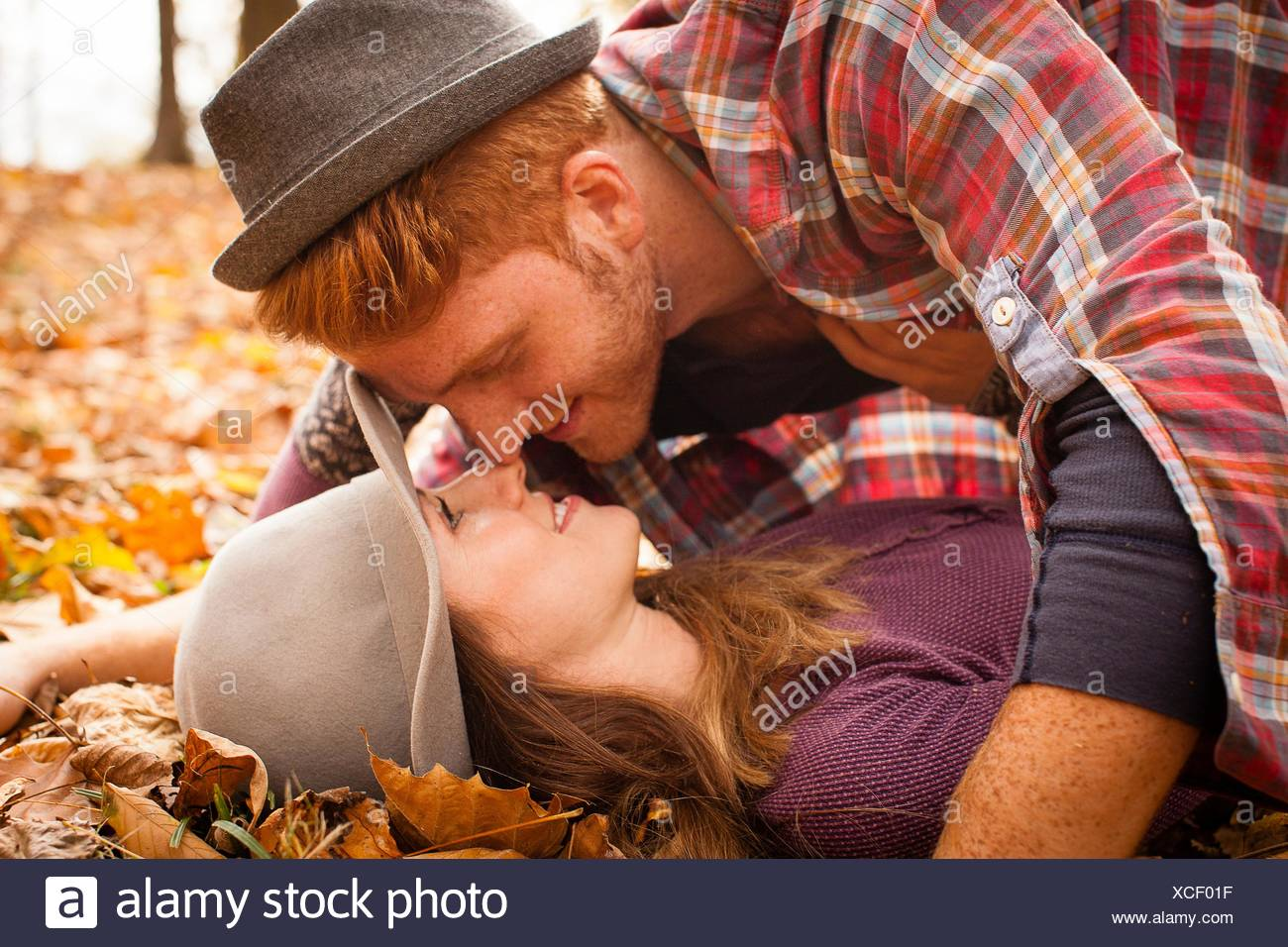 Young couple face to face on autumn forest floor - Stock Image
