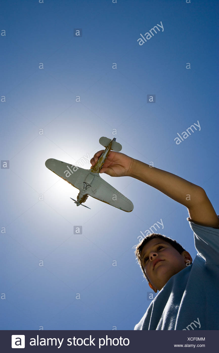 Boy  playing with toy aeroplane against clear blue sunlit sky, upward view backlit - Stock Image