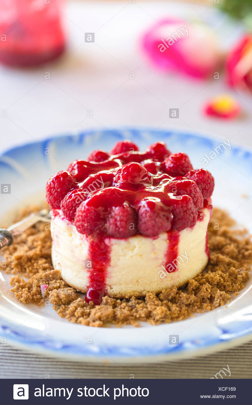 raspberry topped cheesecake on blue motif plate - Stock Image
