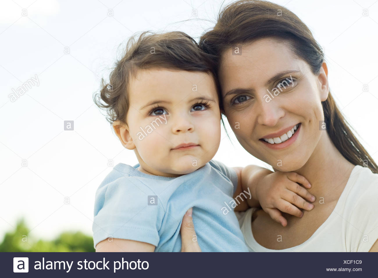 Mother holding baby, smiling at camera, portrait - Stock Image