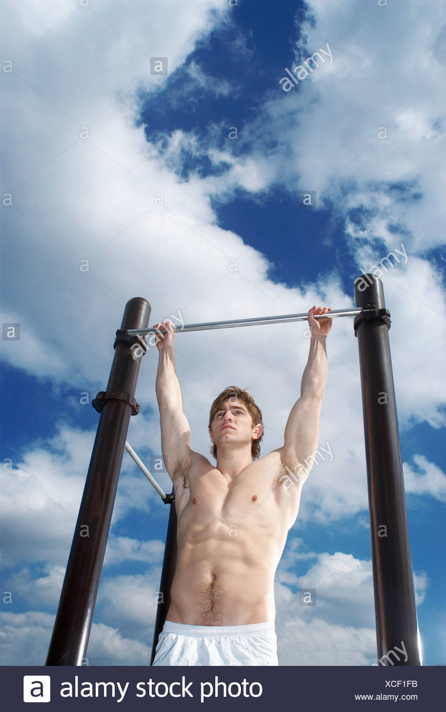 man hanging on pull up bar - Stock Image