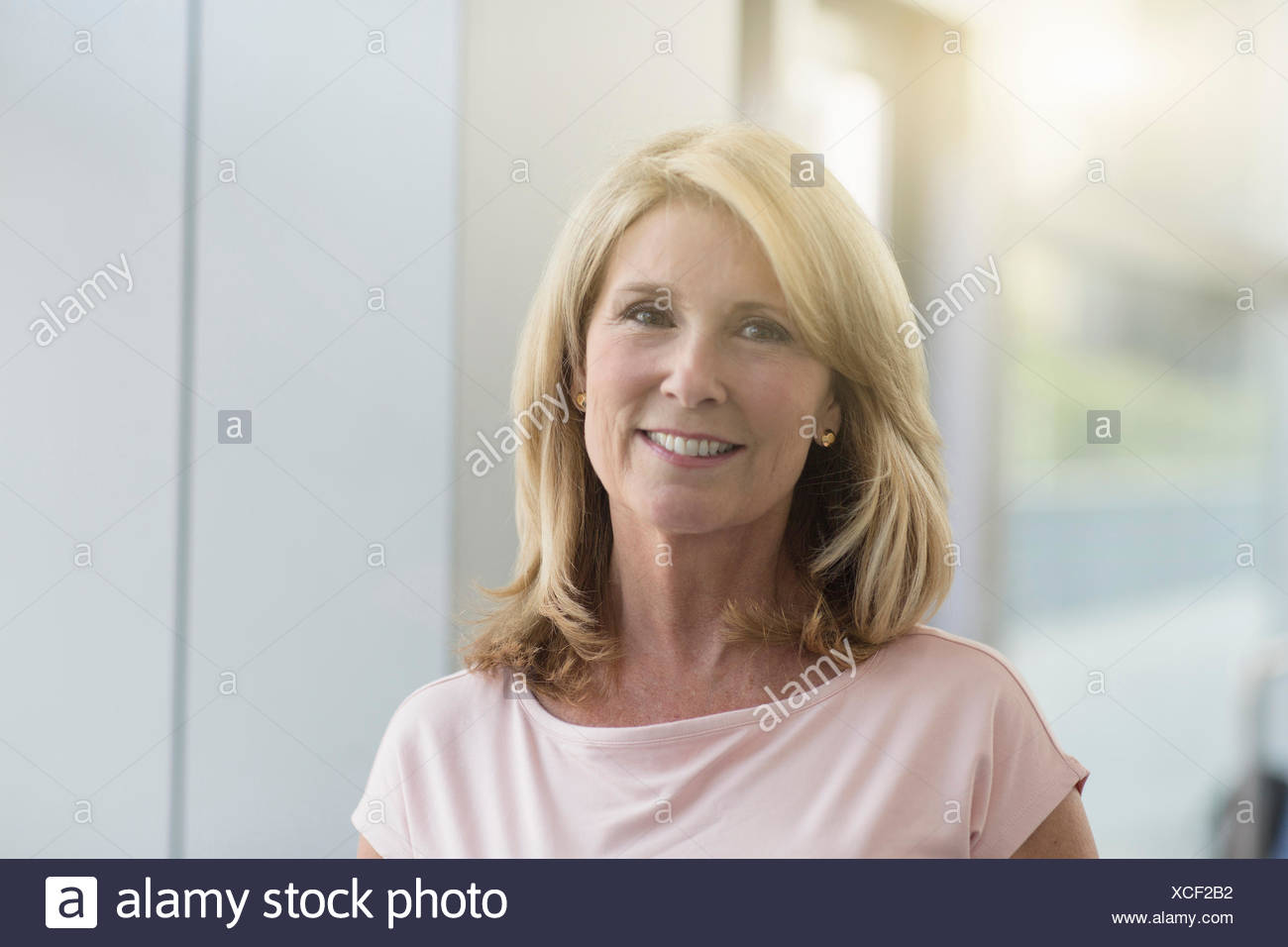 Mature woman with blonde hair, portrait - Stock Image