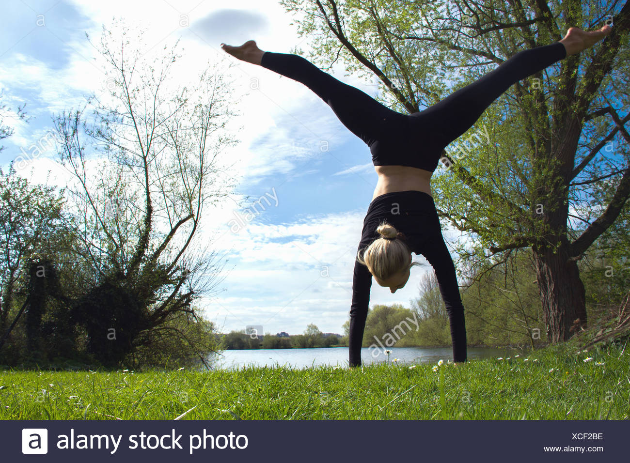 Young female dancer poised in handstand near lake - Stock Image