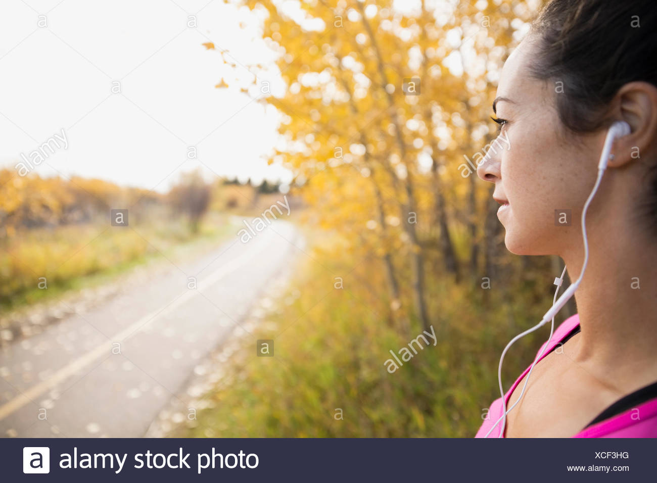Jogger with headphones looking at autumn path - Stock Image