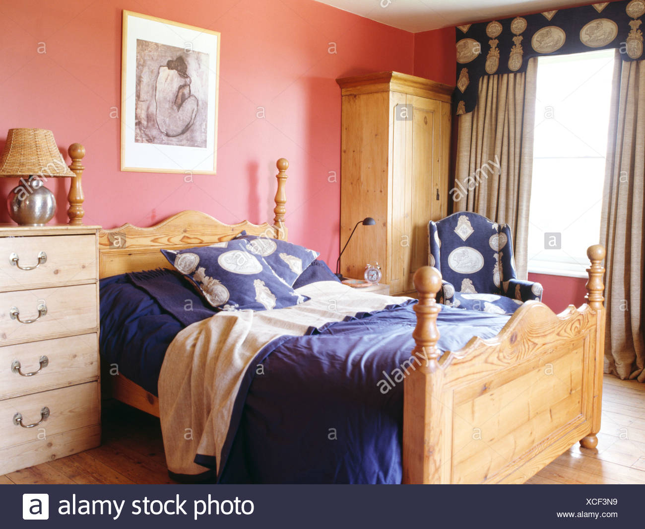 Pine bed with blue cushions and bedlinen in pink bedroom ...