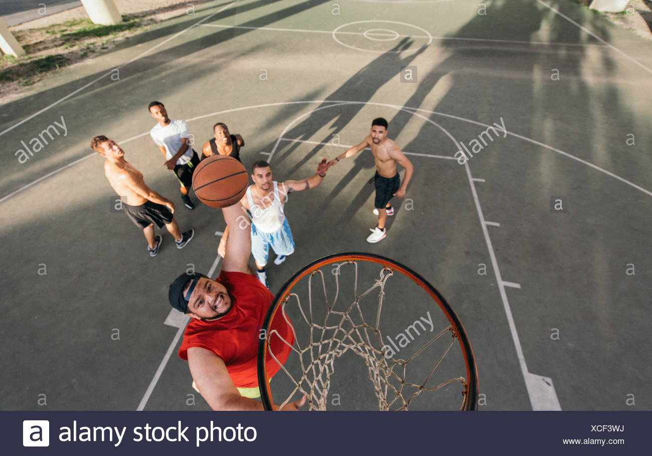 High angle view of young man on basketball court doing slam dunk - Stock Image