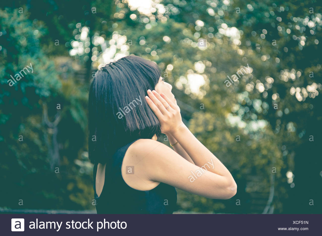Close-Up Of Woman Looking Away Against Trees - Stock Image