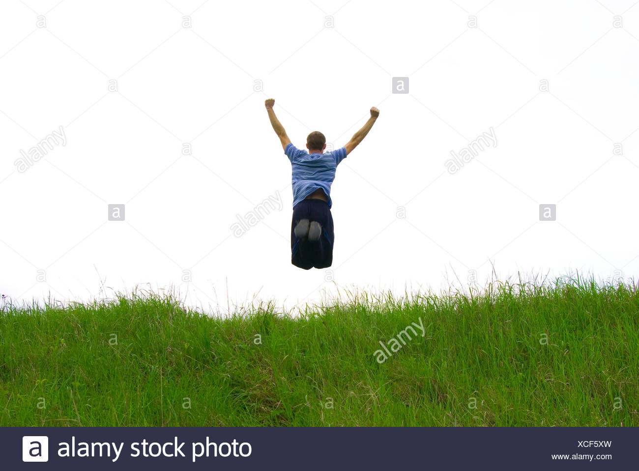 Young guy in jump on background field - Stock Image