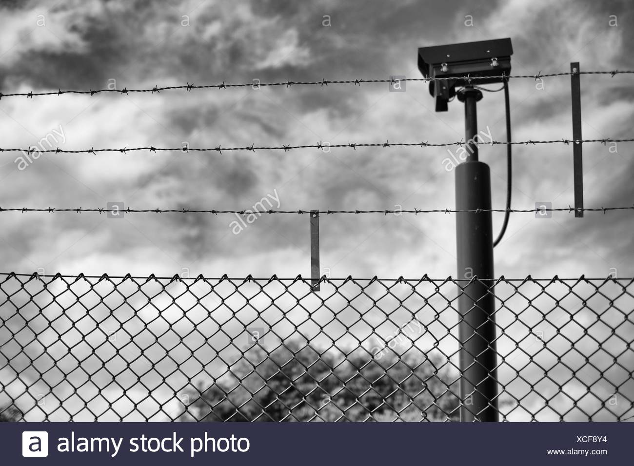 Barbed Wire Fence And Surveillance Camera - Stock Image