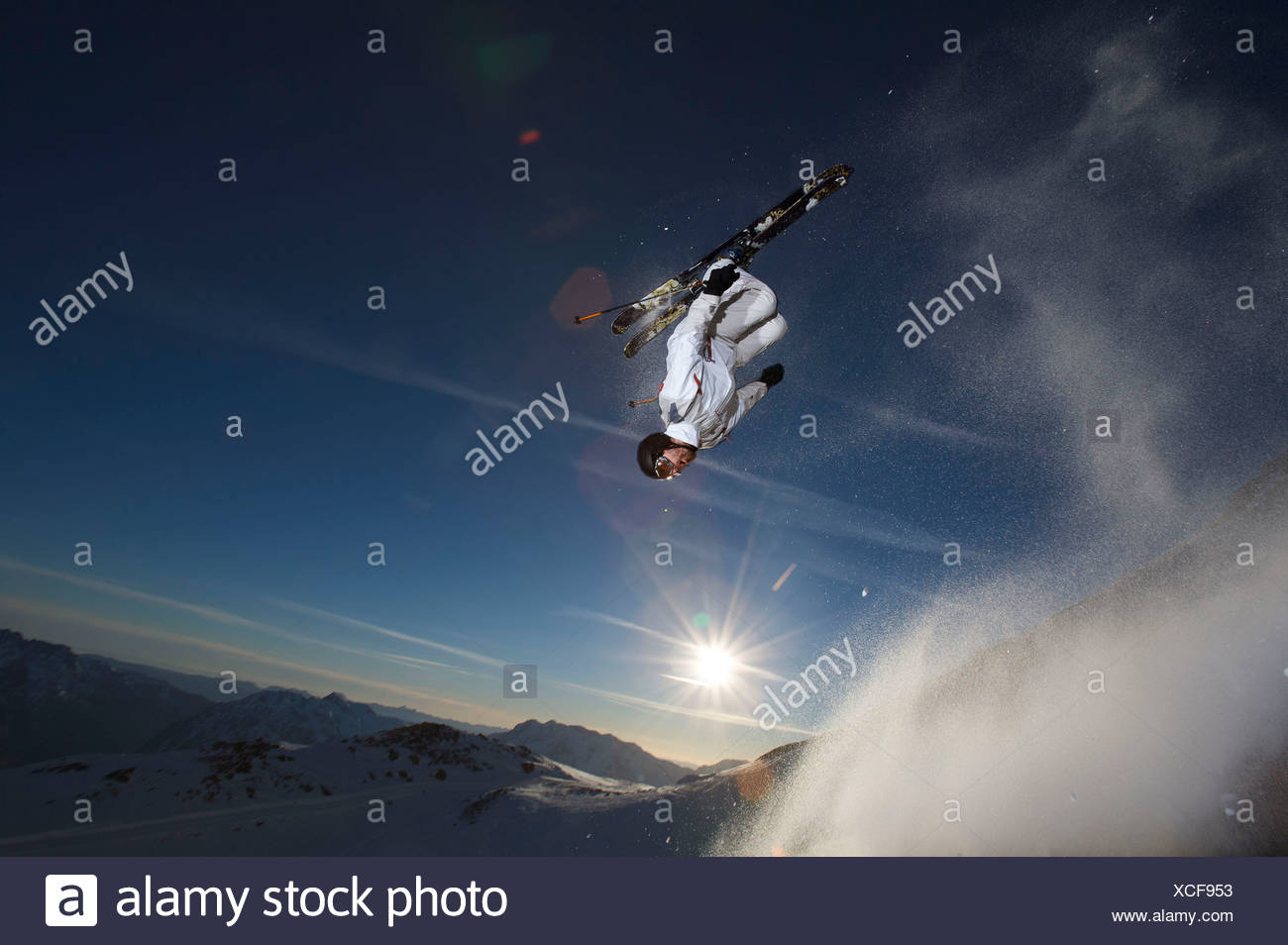 Skier back flipping off a rock. - Stock Image