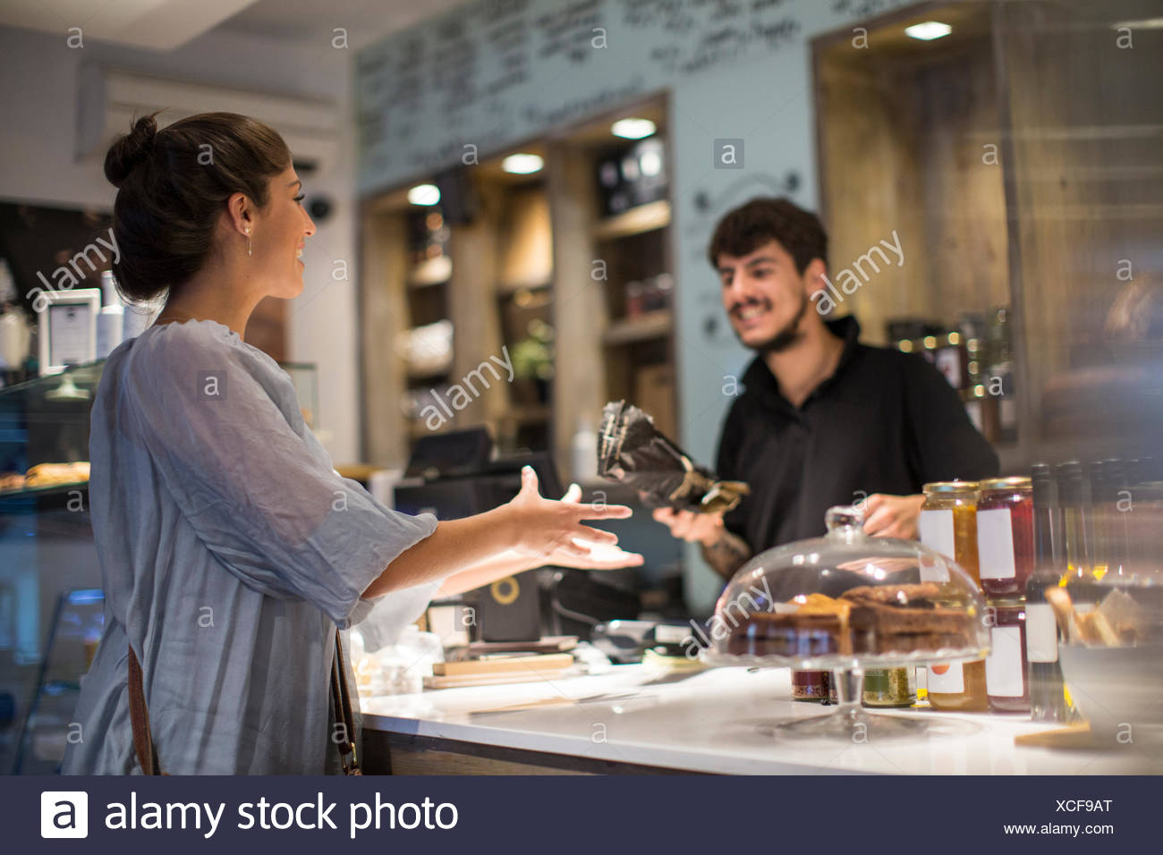 Barista handing baguette to female customer at cafe counter - Stock Image