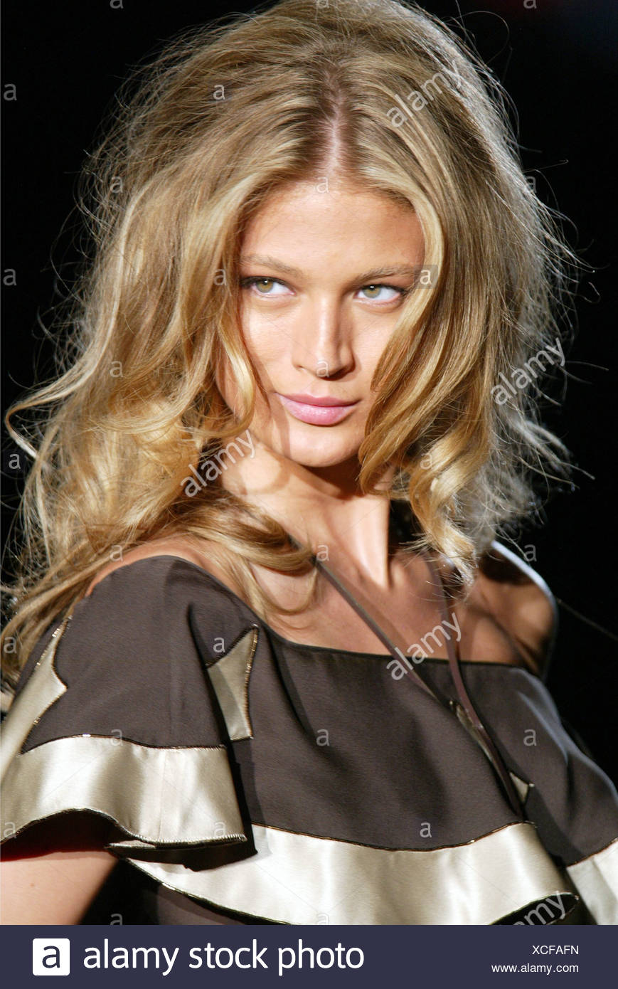 DSquared Milan Ready to Wear S S Blonde female big tousled hair wearing satin brown frilly outfit, accessorised a bola tie - Stock Image