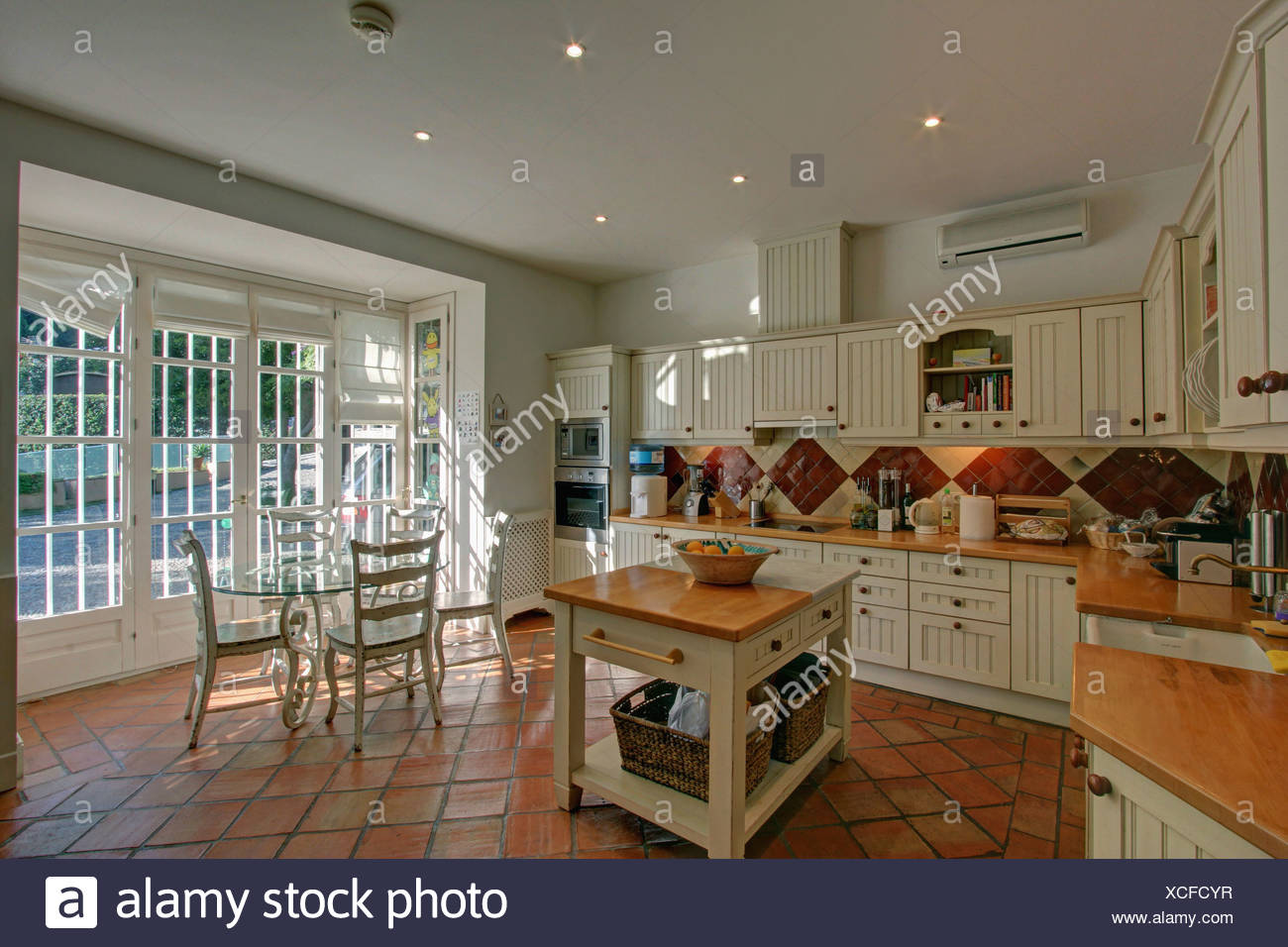 Butcher S Block In Country Style Spanish Kitchen With Terracotta Tiled Floor And Glass Dining Table With White Chairs Stock Photo Alamy