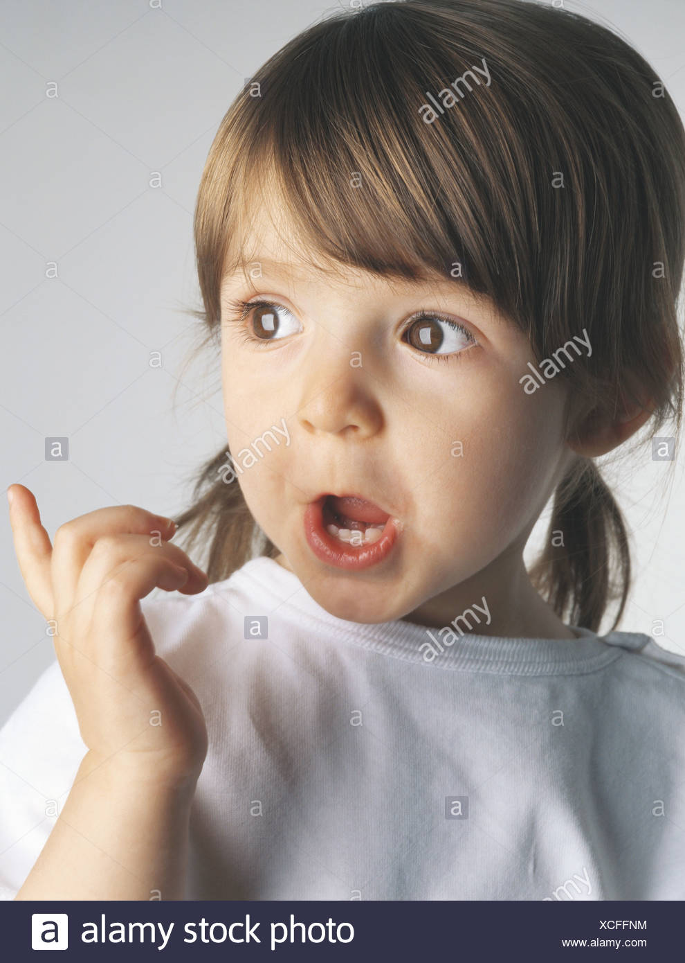 Little girl making face and pointing, portrait - Stock Image