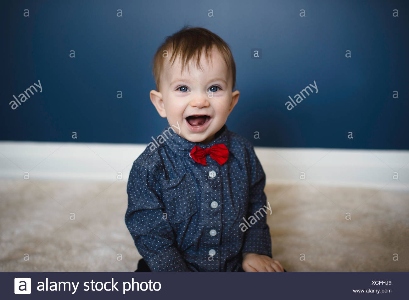 Portrait of male toddler in red bow tie sitting on floor - Stock Image