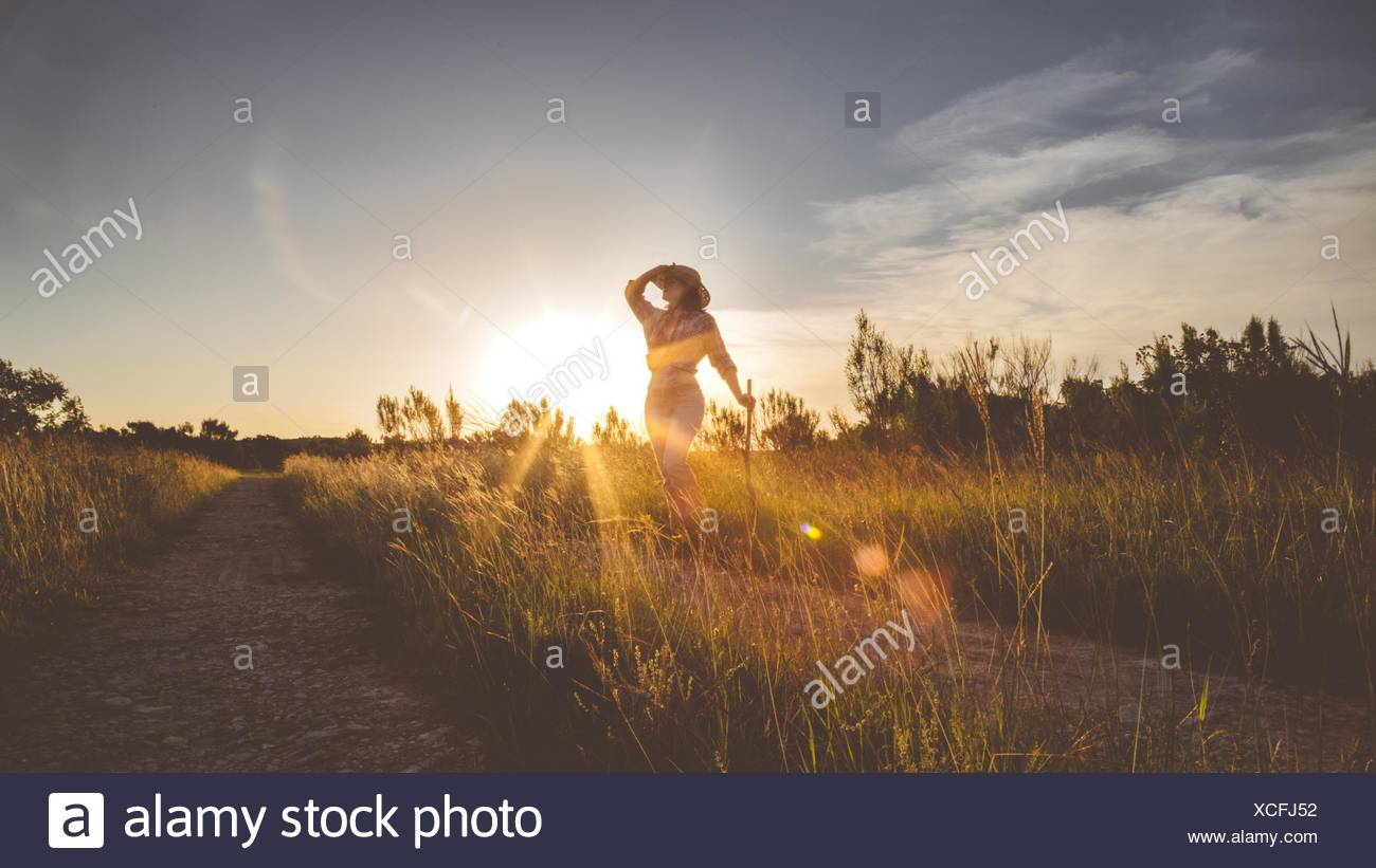 Woman Posing While Standing On Field Against Sky At Sunset - Stock Image