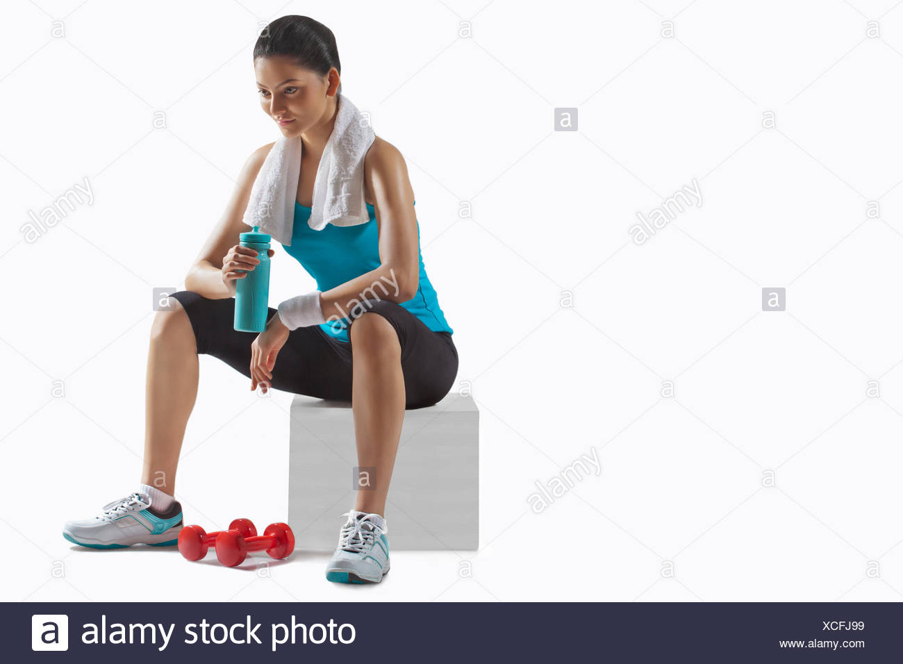Fit young woman holding water bottle while lost in thoughts over white background - Stock Image