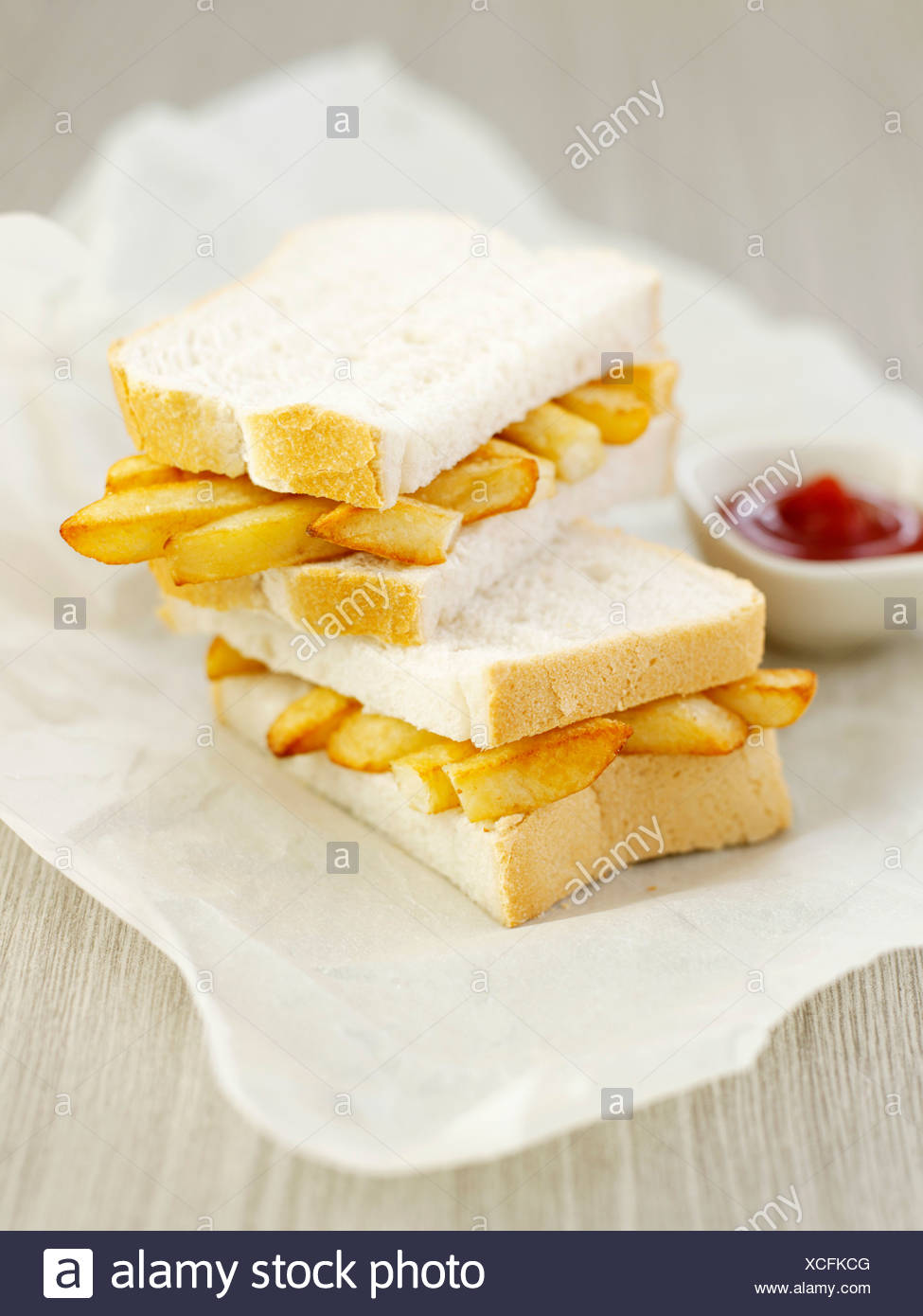 Chip butty, halved, on paper with dish of ketchup - Stock Image
