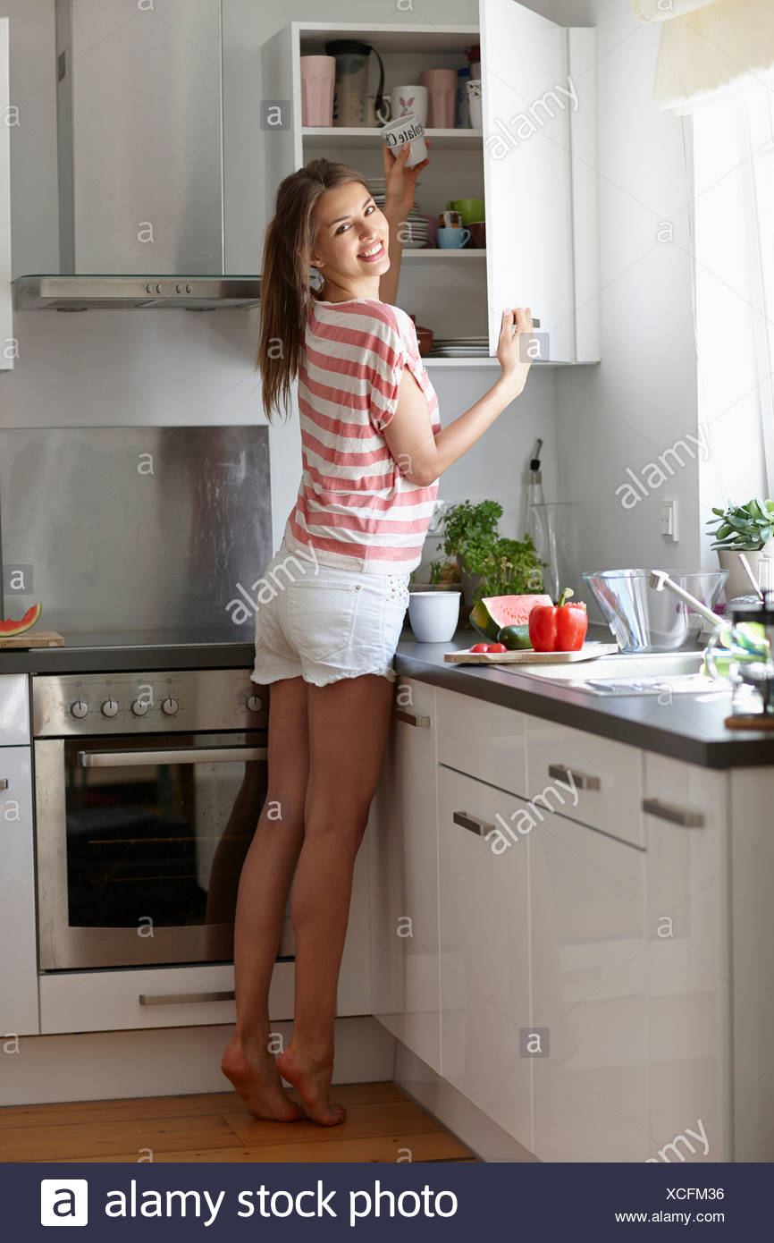 Woman taking mug from cabinet - Stock Image