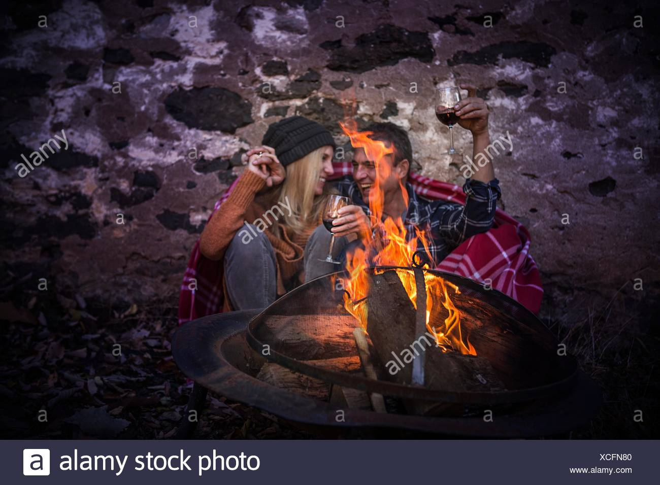Romantic mature couple wrapped in blanket in front of campfire at night - Stock Image