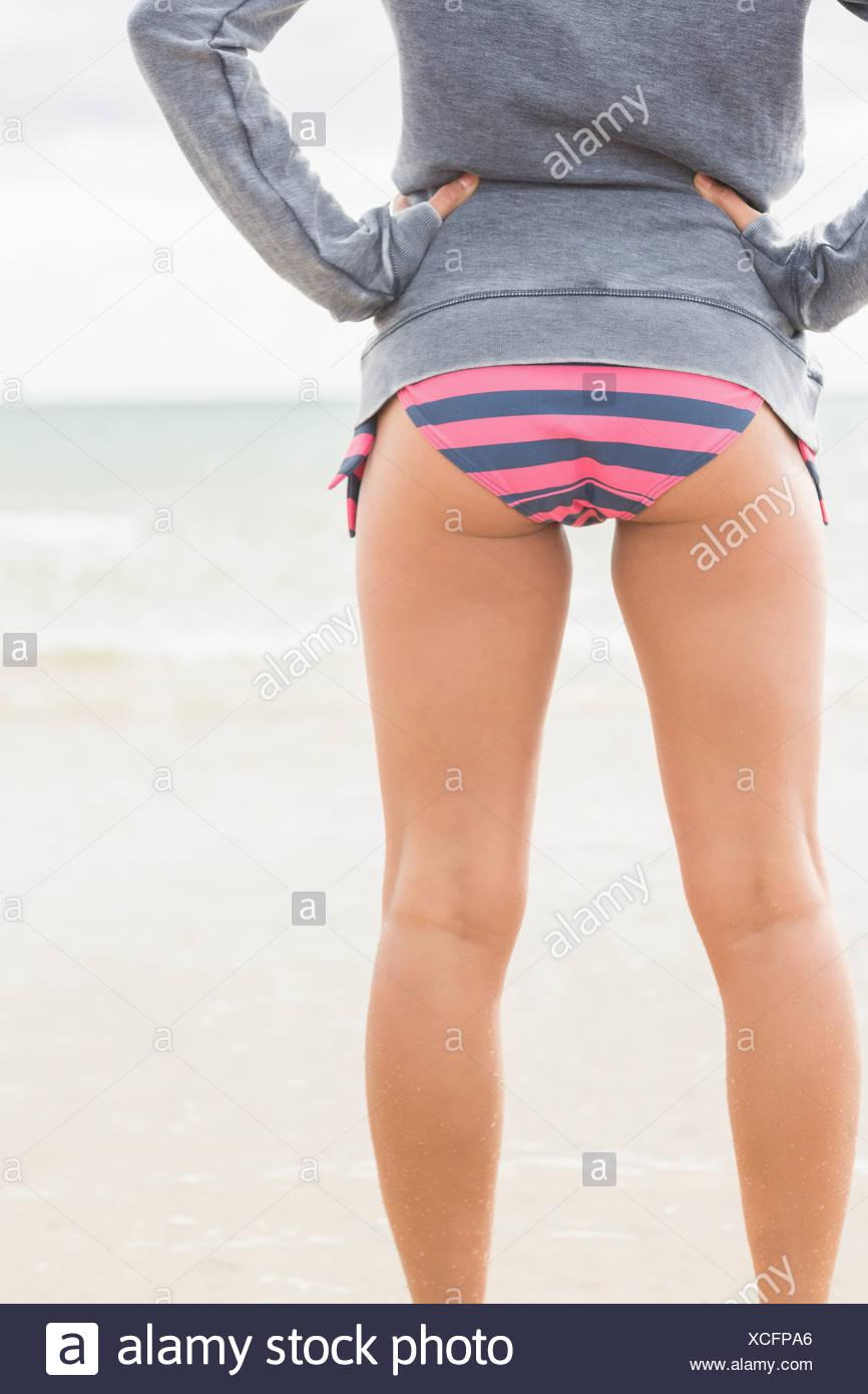 Slender woman in bikini bottom and gray jacket at beach - Stock Image