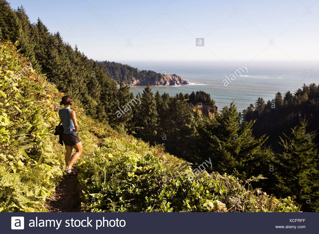 A woman wearing summer clothes hikes Neahkahnie Mountain, a coastal trail in northwest Oregon, and pauses to look out over the o - Stock Image