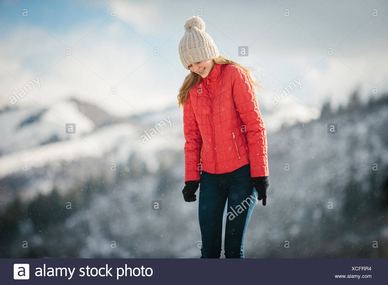 A young girl in a red coat and woolly hat outdoors in the winter. - Stock Image