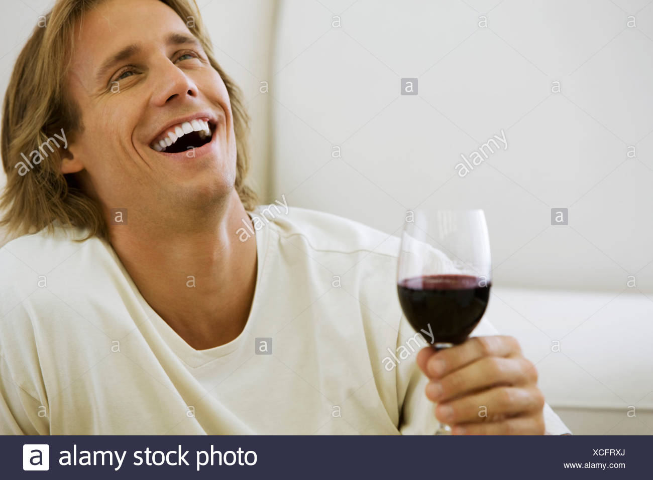 Man holding glass of red wine, laughing - Stock Image