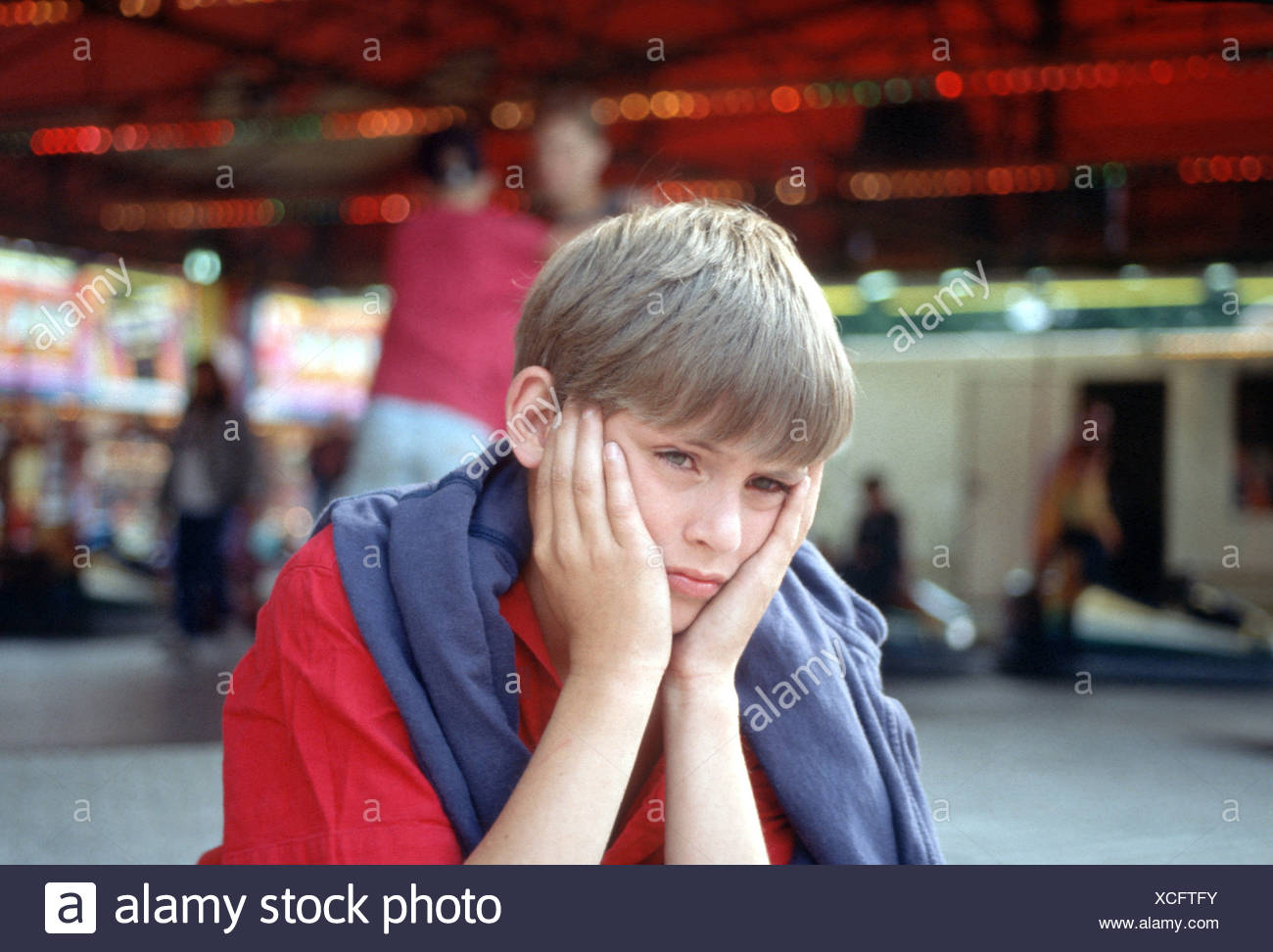 Depressed boy at fairground Stock Photo