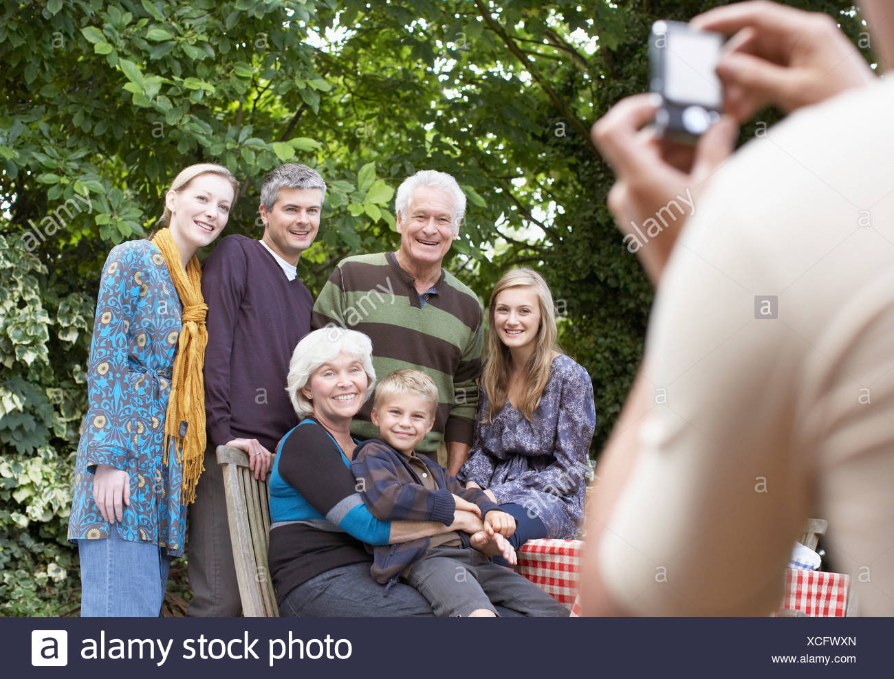 Man taking photograph of family - Stock Image