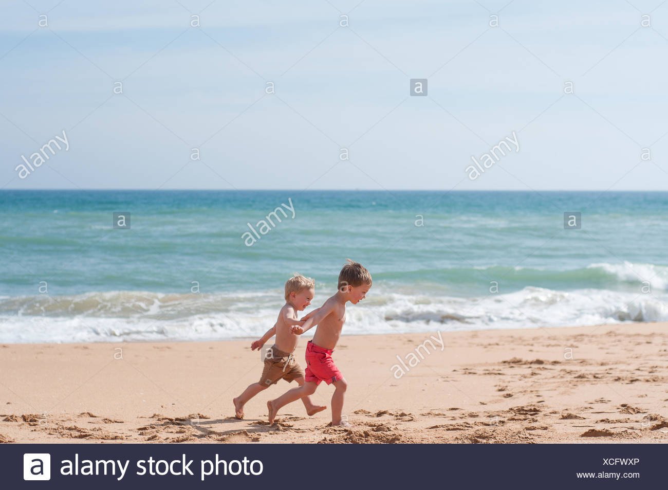 Two boys running along the beach - Stock Image
